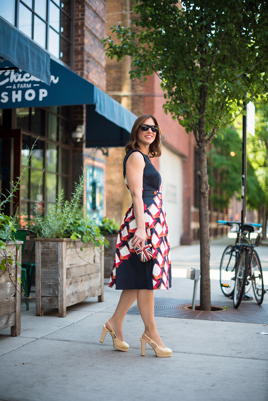 Anna Roufos Sosa of Noir Friday in a printed Suno dress, Alexander McQueen clutch and Chanel pumps.