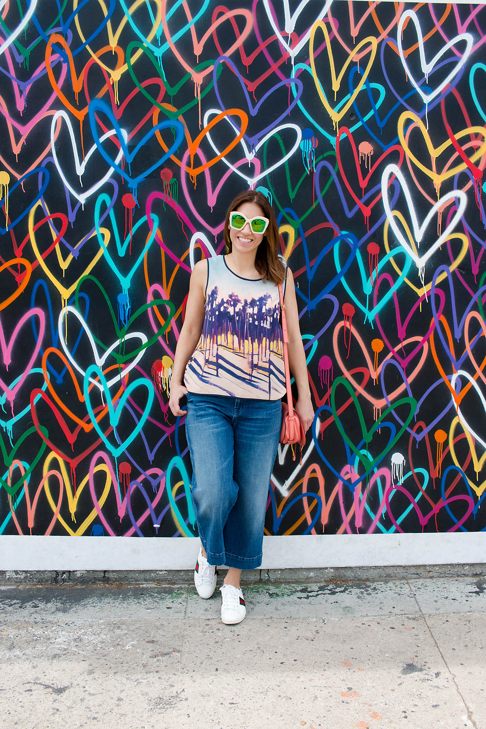 Anna Roufos Sosa in front of a heart print wall in LA wearing Mother of Pearl and Gucci.